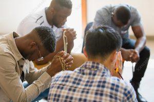 Men praying with rosaries in prayer group.