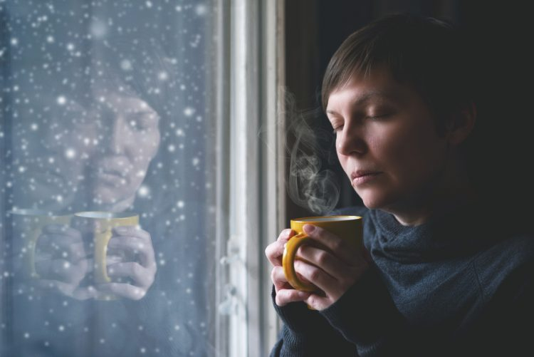 Lonelsome woman drinking cup of coffee by the window of her living room while the snow is falling outside. Selective focus with shallow depth of field.