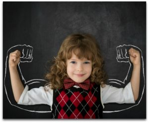 Strong kid in class. Happy child against blackboard. Education concept