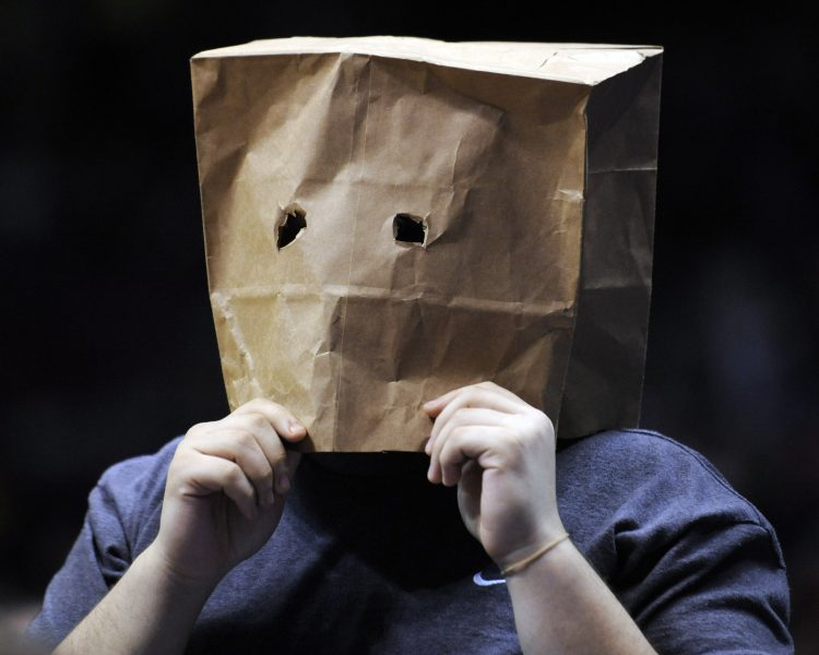 A fan with a paper bag over his head watches during the fourth quarter of an NBA basketball game between the New Jersey Nets and the Miami Heat on Monday, March 22, 2010, in East Rutherford, N.J. The Nets have a 7-63 record as the Heat defeated the Nets 99-89.  (AP Photo/Bill Kostroun)